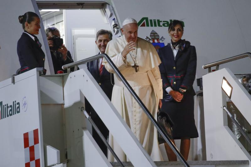 Pope Francis waves as he boards an airplane to Thailand, at the Rome Leonardo da Vinci airport on Tuesday. (AP photo)