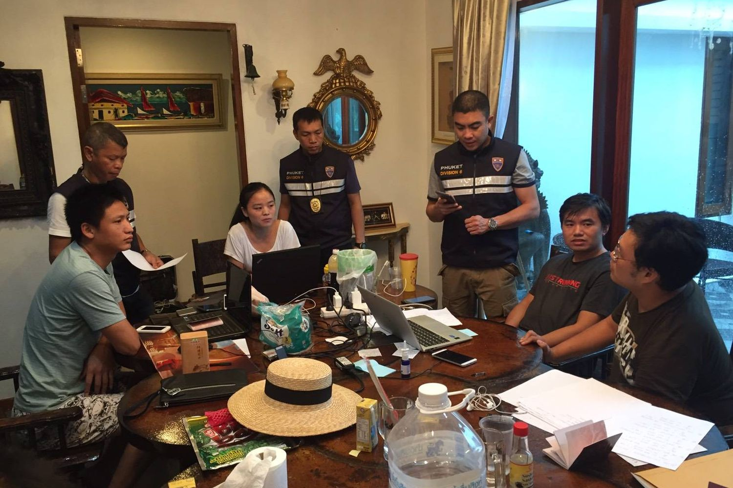 Police talk to fice Chinese caught in Phuket for conducting suspicious businesss involving foreign exgange trading on Thursday. (Photo by Achadtaya Chuenniran)