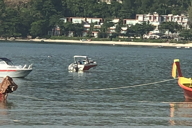 Boats cruise near Kamala beach, where a German tourist was injured by a boat propeller and died later on Friday. (Photo by Achadtaya Chuenniran)