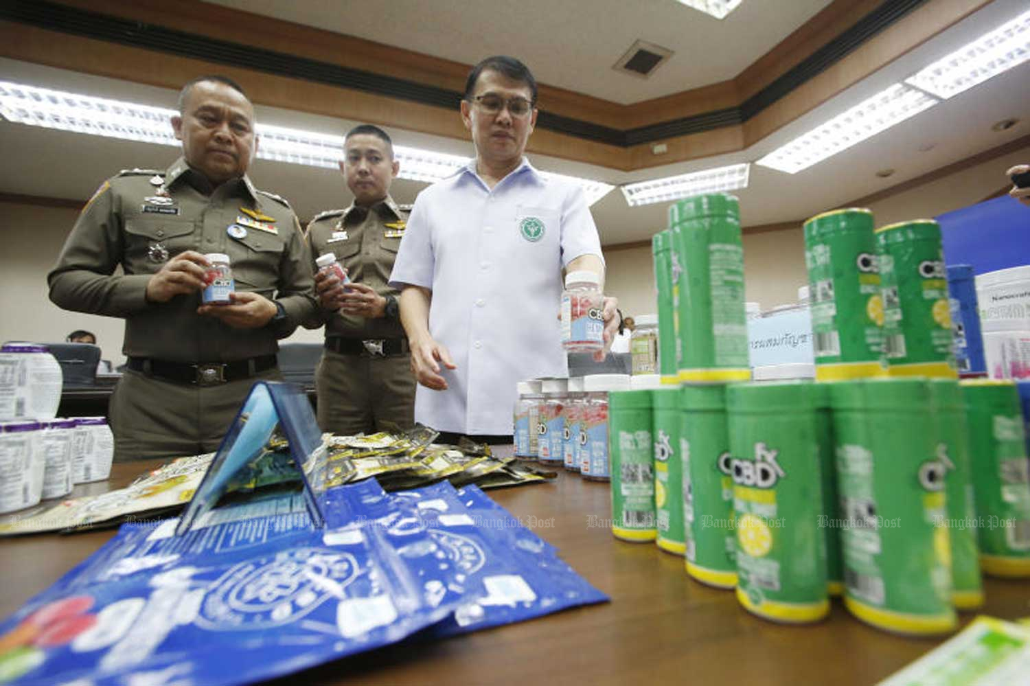 Food and Drug Administration secretary-general Dr Paisarn Dunkum, right, displays products allegedly containing cannabis during a press conference at the FDA head office in Nonthaburi province. (Photo by Pornprom Satrabhaya)