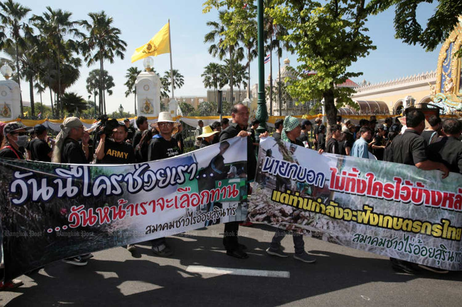 Black-clad farmers holding banners identifying themselves as sugarcane farmers from Surin join the rally against the ban on three farm chemicals, at Government House in Bangkok on Tuesday morning. (Photo by Chanat Katanyu)