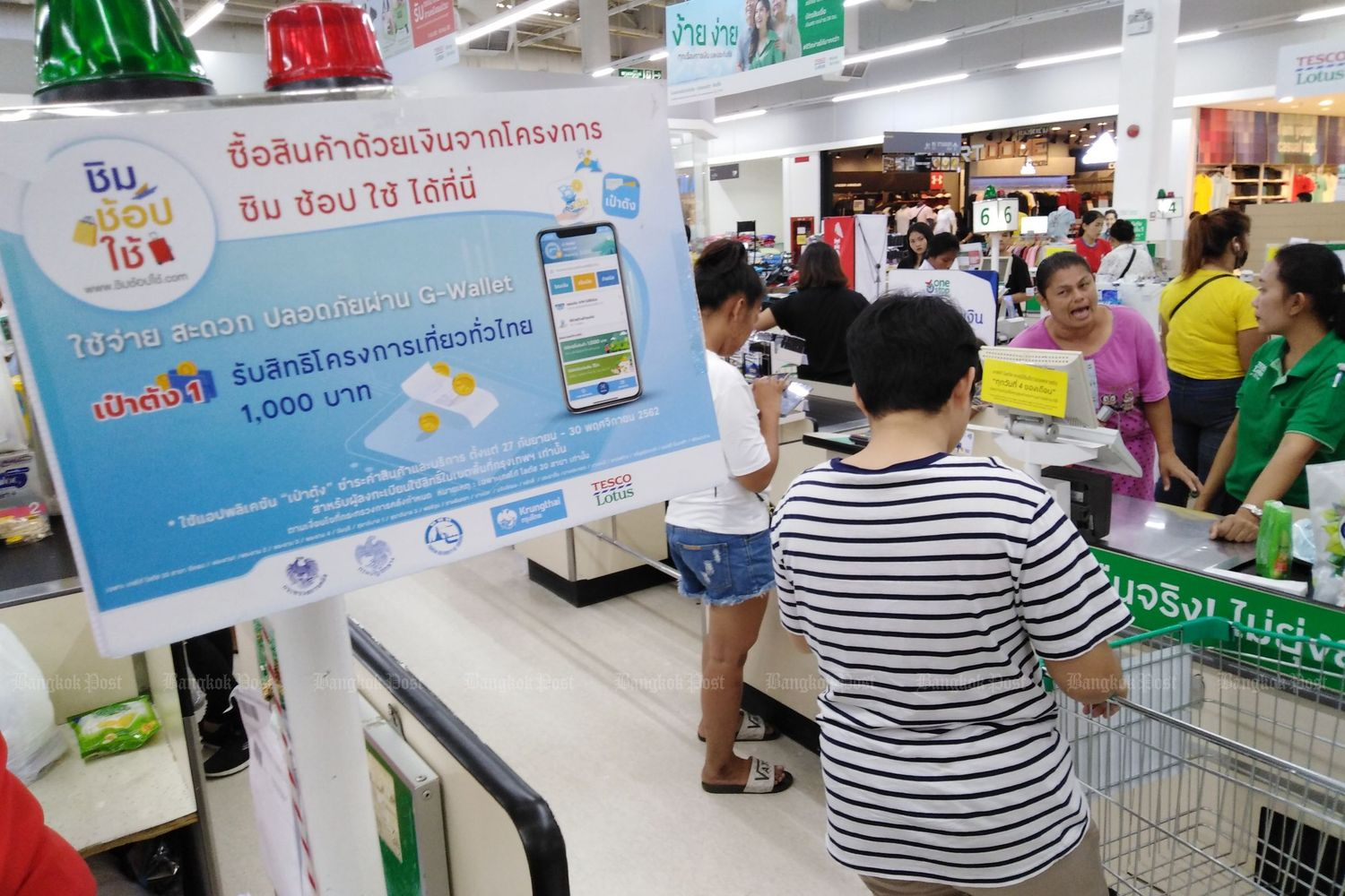 A banner at a Tesco Lotus hypermarket promotes the Taste-Shop-Spend scheme to lure shoppers on Oct 1. (Photo by Pornprom Sattrabhaya)