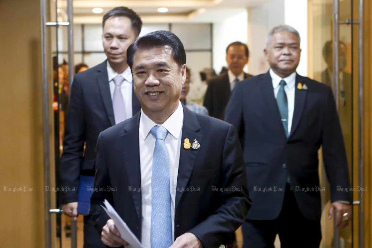 Industry Minister Suriya Juangroongruangkit walks to a press conference at his ministry in Bangkok on Wednesday to announce that the new National Committee on Hazardous Substances has countermanded the total ban on three farm chemicals due to take effect on Sunday. (Photo by Pattarapong Chatpattarasill)