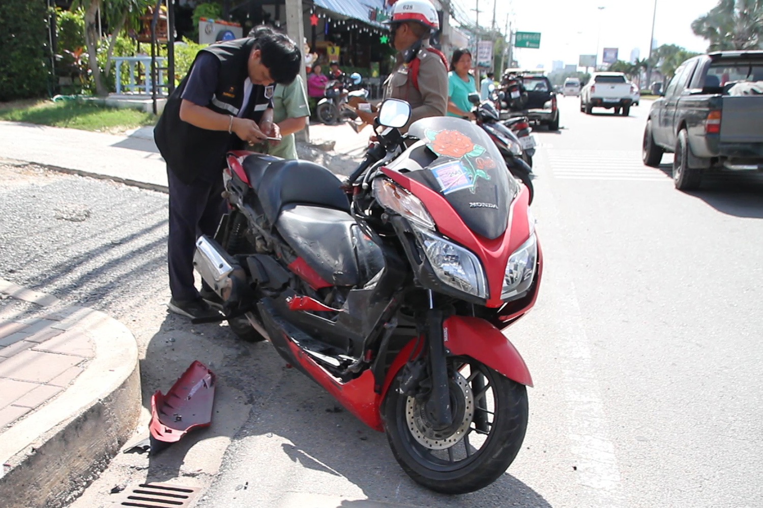 Police and rescue volunteers inspect a motorcycle that collided with a car in Pattaya on Wednesday, killing the bike's driver, Briton John Gresty. (Photo by Chaiyot Pupattanapong)