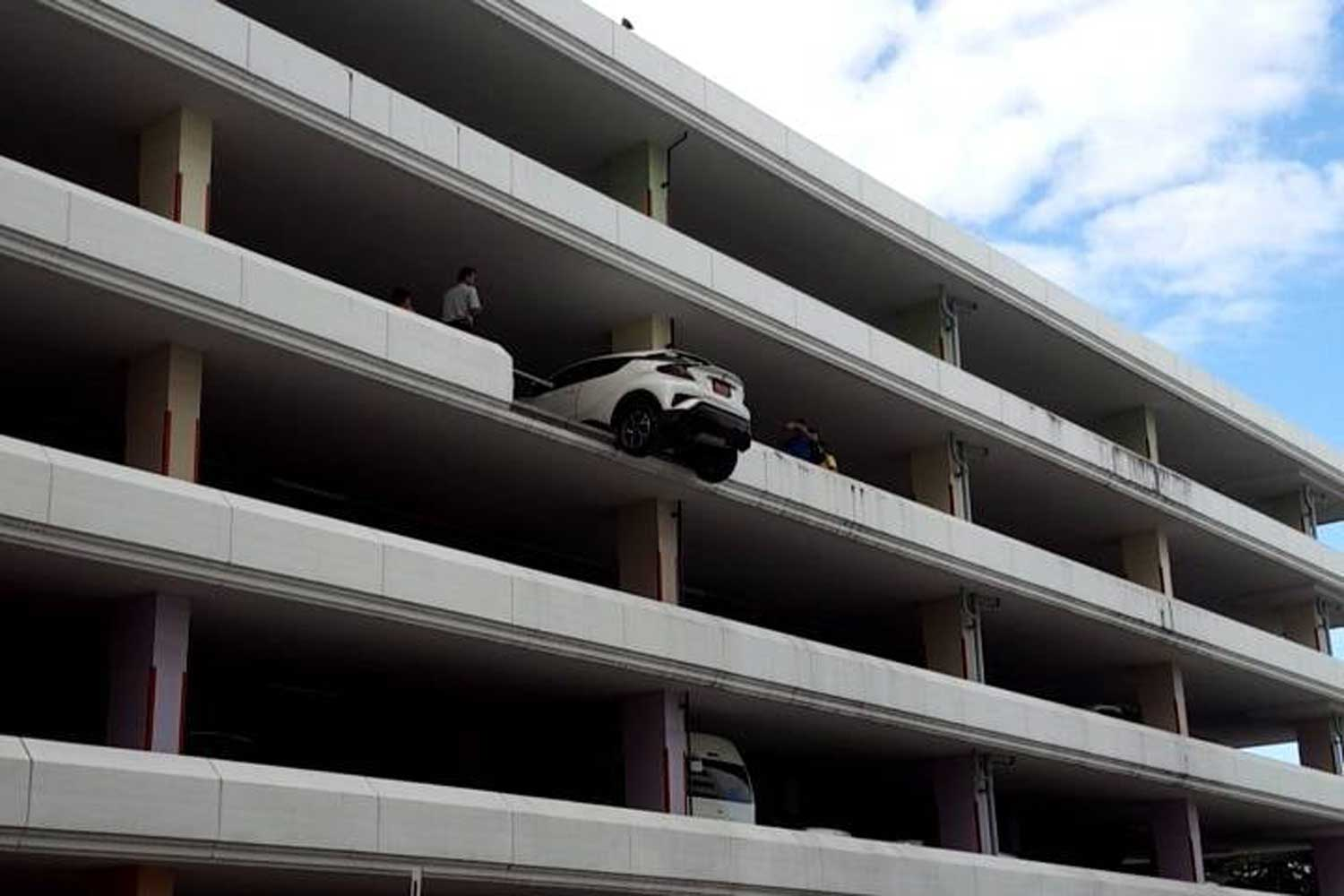 The white Toyota C-HR vehicle stops before falling from the fourth floor of the parking building of the Food and Drug Administration in Nonthaburi province on Thursday morning. (JS100 Radio photos)
