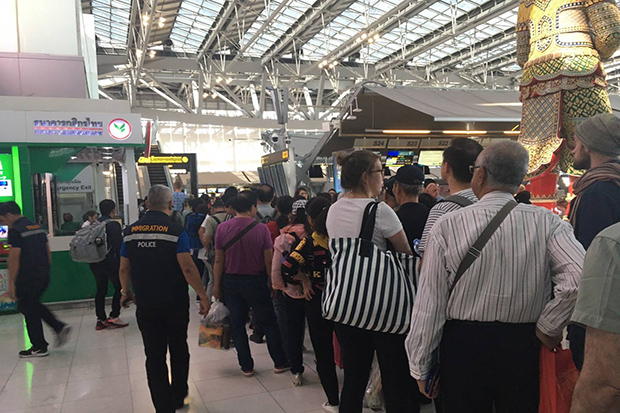 A queue of outbound passengers waiting for security screening is seen at the departure hall of Suvarnabhumi airport on Sunday. (Immigration police photo)
