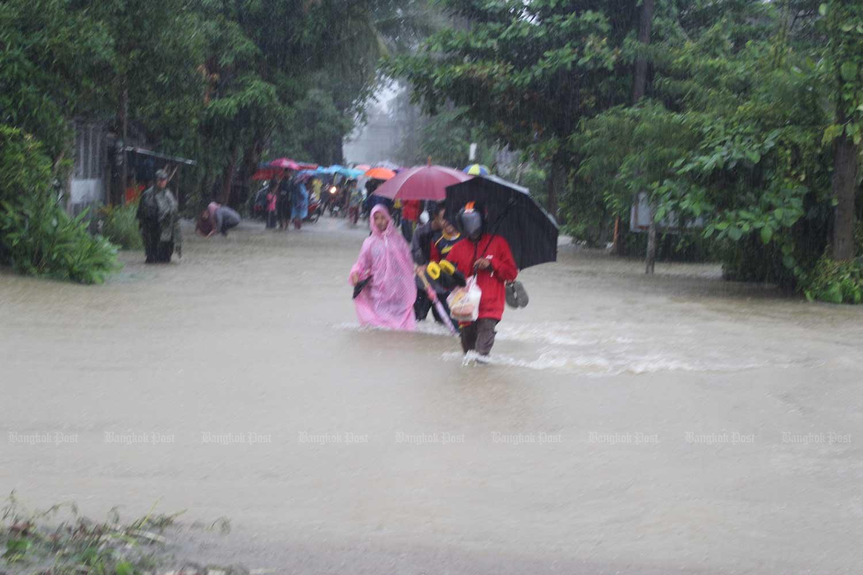 Residents wade through floodwater at Ban Bo Thong of tambon Tanyongmat in Rangae district, Narathiwat, on Monday morning. (Photo by Waedao Harai)