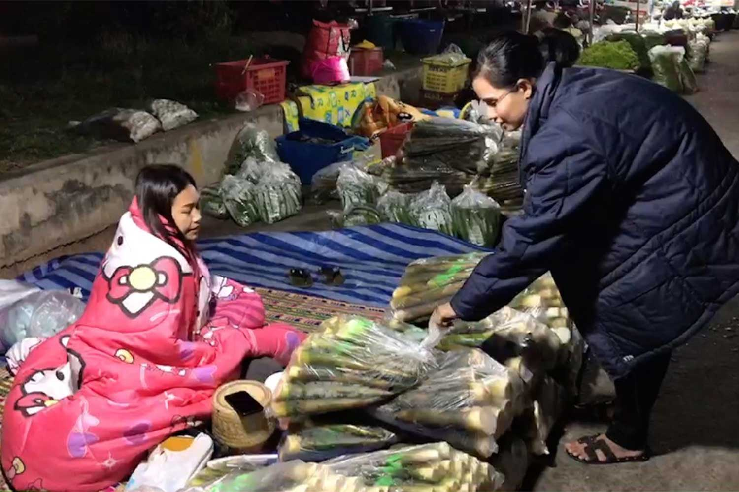 This vegetable vendor and her customer were well wrapped up against the cold at a market in Muang district of Kalasin province early on Tuesday. (Photo by Yongyuth Phuphuangpet)