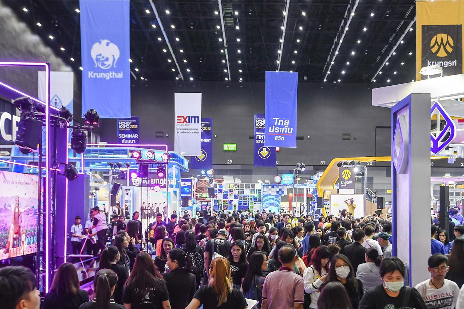 Visitors browse financial services provided by banks during the Money Expo at Bitec. The Bank of Thailand will begin random checks of the fees charged by financial institutions in mid-2020.