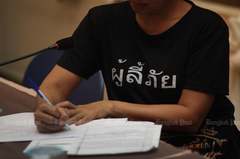 A participant wearing a T-shirt emblazoned with 'Refugees' makes a note at a forum on the condition of refugees along Thai borders in January 2018. (Photo by Thiti Wannamontha)