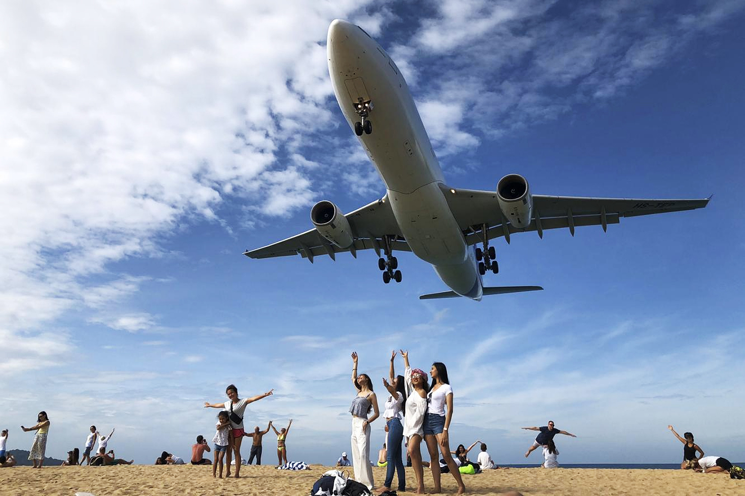 Tourists on Mai Khao beach pose for a picture as a jet comes in to land at Phuket International Airport. The beach is a popular destination for tourists looking to snap selfies as the planes approach directly overhead.(Photo by Sarot Meksophawannakul)