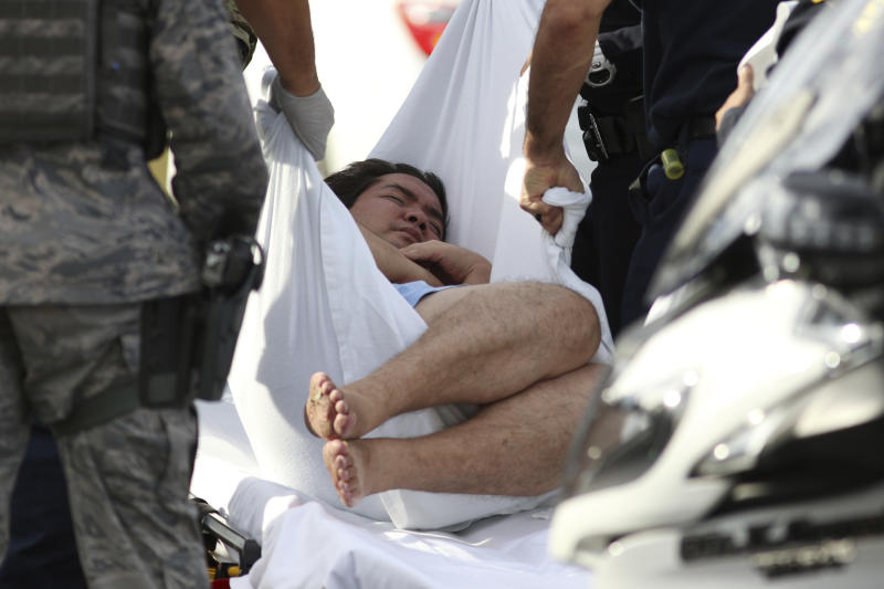An unidentified male is taken away by officers outside the main gate at Joint Base Pearl Harbor-Hickam on Wednesday in Hawaii, following a shooting. (AP photo)