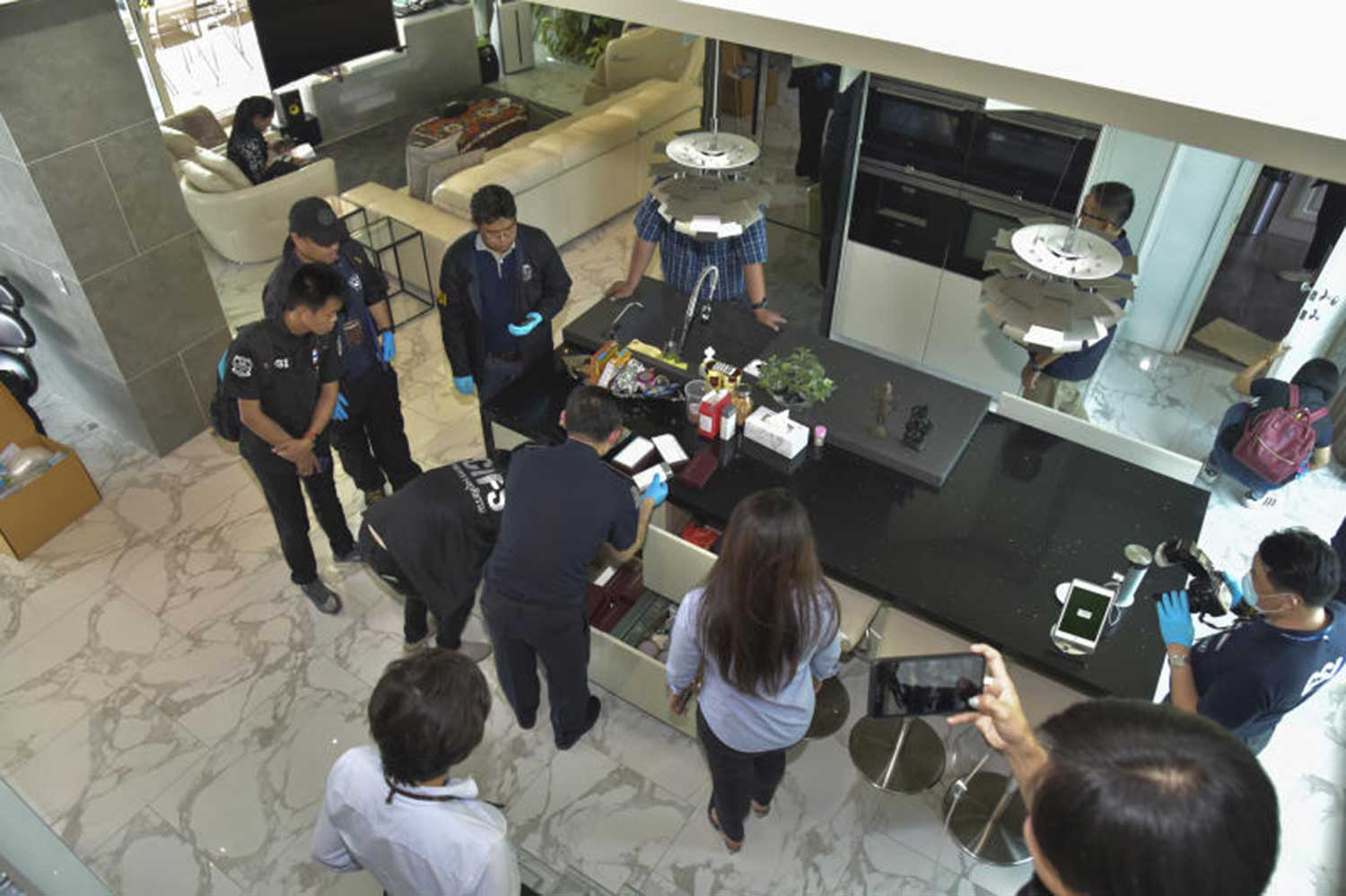 Officials from the Department of Special Investigation search a house in Bangkok to find evidence involving the Forex-3D scam in Bangkok on Nov 22. On Wednesday, the DSI searched four more locations and seized 15.3 million baht worth of assets from those accused of being behind the online broker Forex-3D scam. (DSI photo)