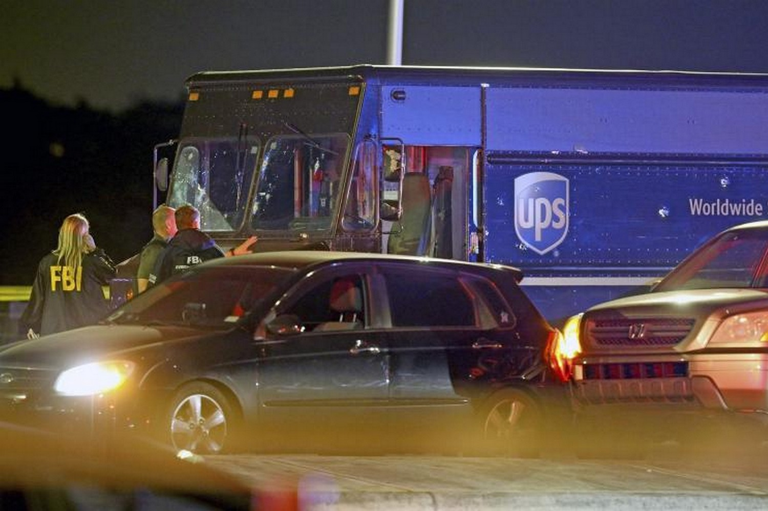 Law enforcement officers stand near a UPS vehicle that appears to be part of the crime scene where four people were killed in Miramar, near Miami, on Thursday after robbers led police on a chase that ended in gunfire at a busy Florida intersection during rush hour.(Photo: Miami Herald/AP)