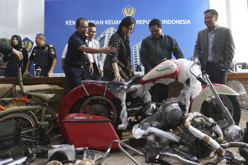 Indonesian Finance Minister Sri Mulyani Indrawati (third from right) and Minister of State-Owned Enterprises Eric Thohir (second from right) inspect a Harley Davidson motorcycle found by Customs officials on a Garuda Indonesia's new Airbus A330-900 being delivered from France, prior to the start of a press conference in Jakarta on Thursday. (AP photo)