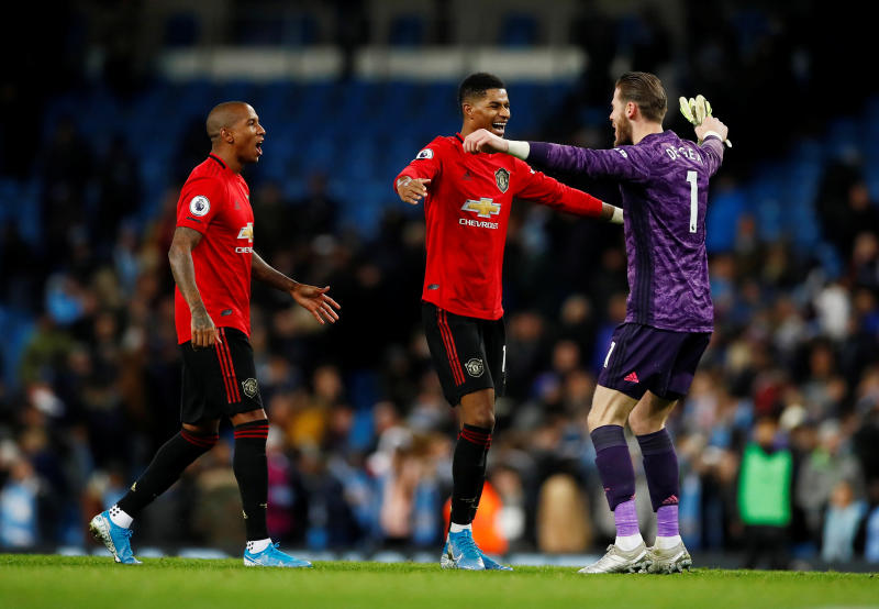 Manchester United's Marcus Rashford (centre), Ashley Young and David de Gea celebrate after the match against Manchester City at Etihad Stadium on Saturday. (Reuters photo)
