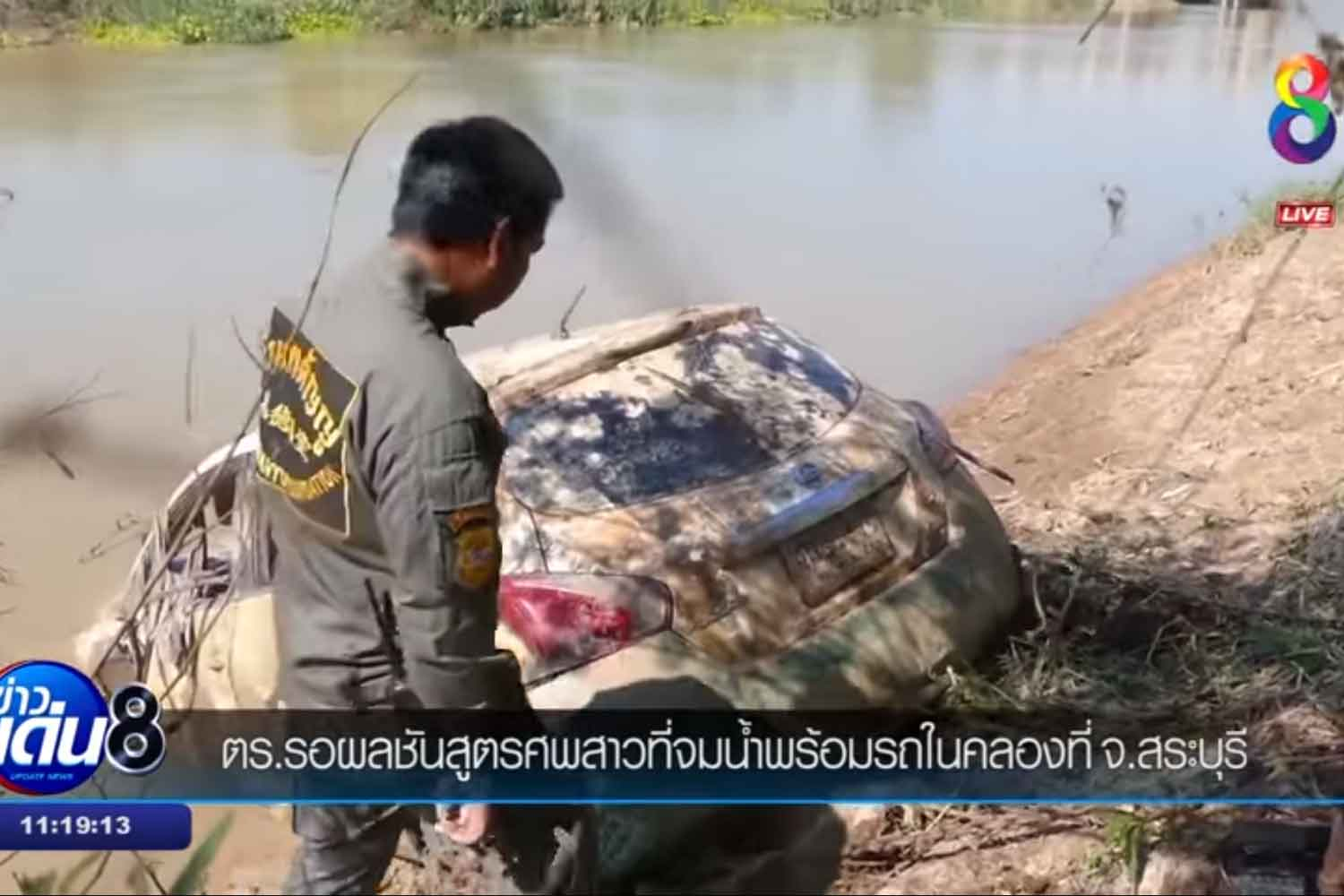 A rescue worker looks at a white Nissan Pulsar car hauled out of an irrigation canal in Nong Don district of Saraburi on Monday. A human skeleton wrapped in a bed sheet was found inside. (Screenshot from TV channel 8)