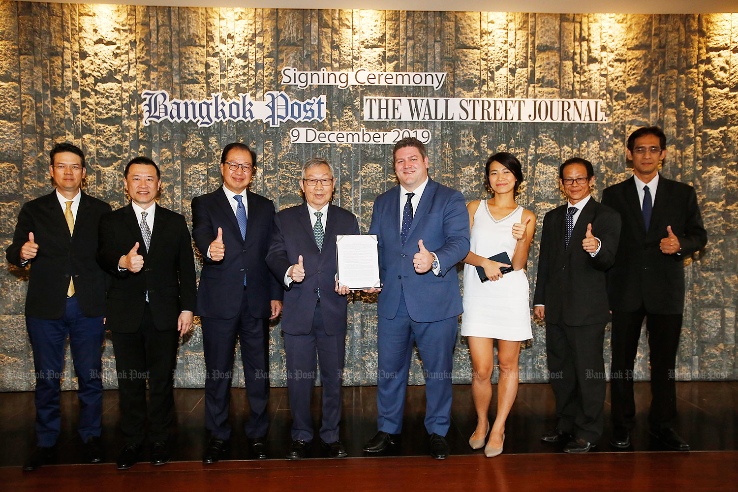 Suthikiati Chirathivat, 4th left, chairman of Bangkok Post Plc, and Jonathan Wright, 4th right, global managing director for Dow Jones and the Wall Street Journal, hold a partnership contract after the signing ceremony at Centara Grand at CentralWorld. The ceremony was attended by Thirakiati Chirathivat, left, executive director of Bangkok Post Plc; Ek-Rit Boonpiti, 2nd left, executive director of Bangkok Post Plc; Worachai Bhicharnchitr, 3rd left, Bangkok Post Plc's vice-chairman; Esme Choi, 3rd right, Asia Pacific manager of Commercial Partnerships, Dow Jones; Chiratas Nivatpumin, 2nd right, acting COO of Bangkok Post Plc and Soonruth Bunyamanee, right, the Bangkok Post's editor. (Photo by Pornprom Satrabhaya)
