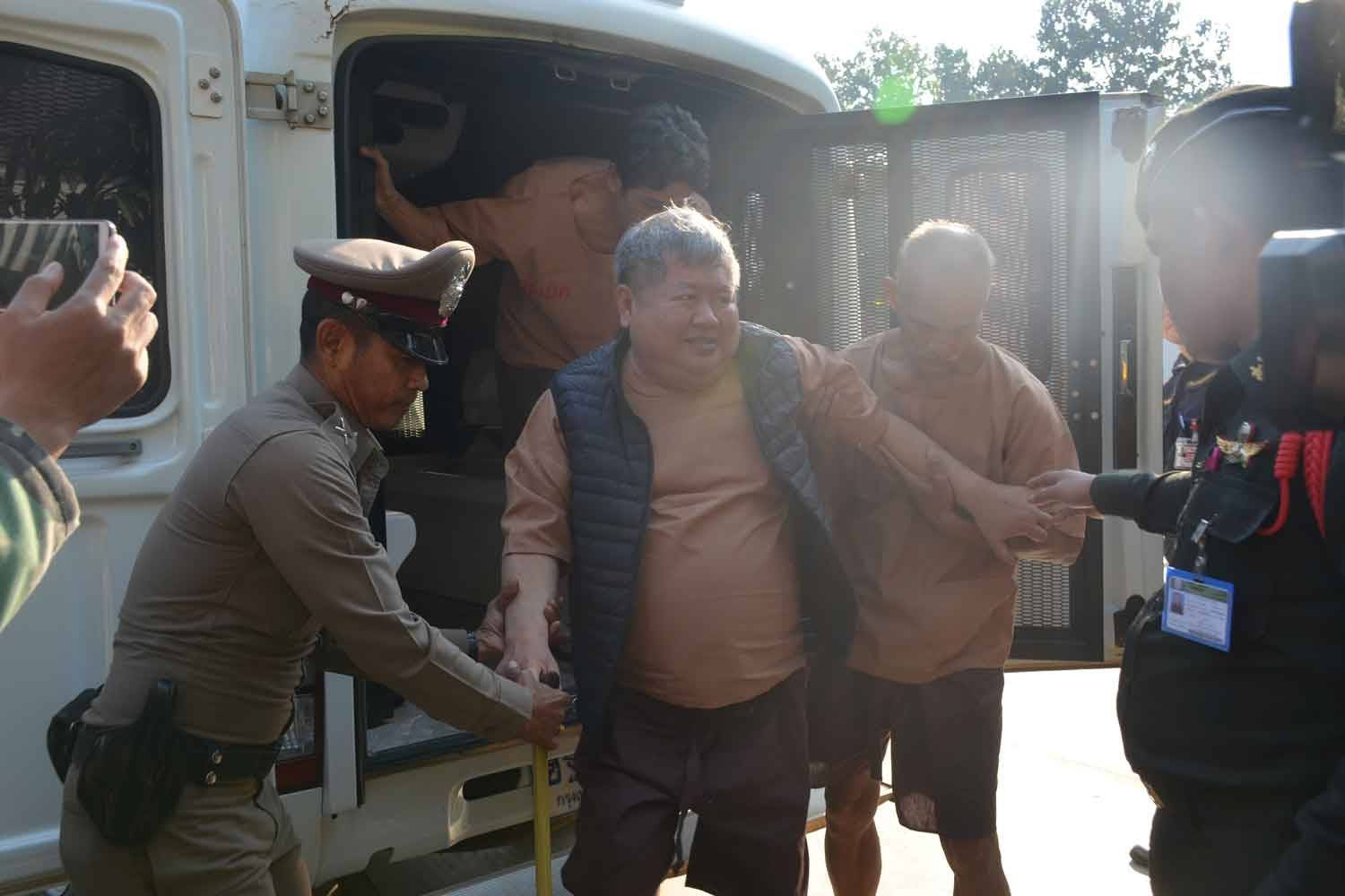 Construction billionaire Premchai Karnasuta is helped out of the prison truck as he arrives at the Thong Pha Phum Court in Kanchanaburi province on Friday morning. (Photo by Piyarat Chongcharoen)