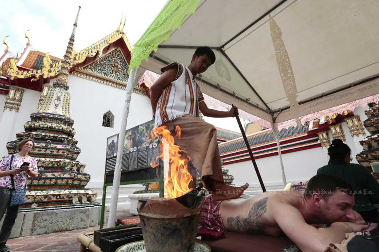 A masseur uses his feet to ease aches in a tourist's back during the Thai traditional medicine fair at Wat Phra Chetuphon (Wat Pho) in Bangkok from Oct 29-Nov 3 this year. (File photo)