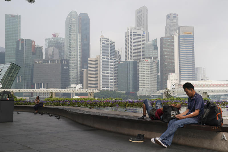 Singaporeans sit next to a  pool as the central business district is shrouded by haze in September this year. The haze was among the top five searches on Google in the city-state. (AP photo)