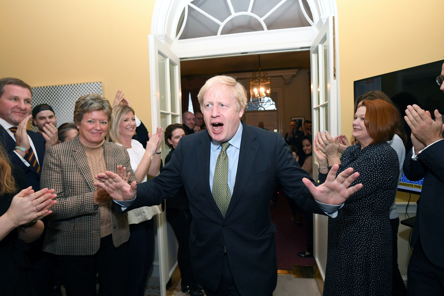 Staff applaud Prime Minister Boris Johnson as he arrives back at Downing Street after meeting Queen Elizabeth and accepting her invitation to form a new government after his Conservative Party won the biggest majority since Margaret Thatcher in 1987. (Reuters Photo)
