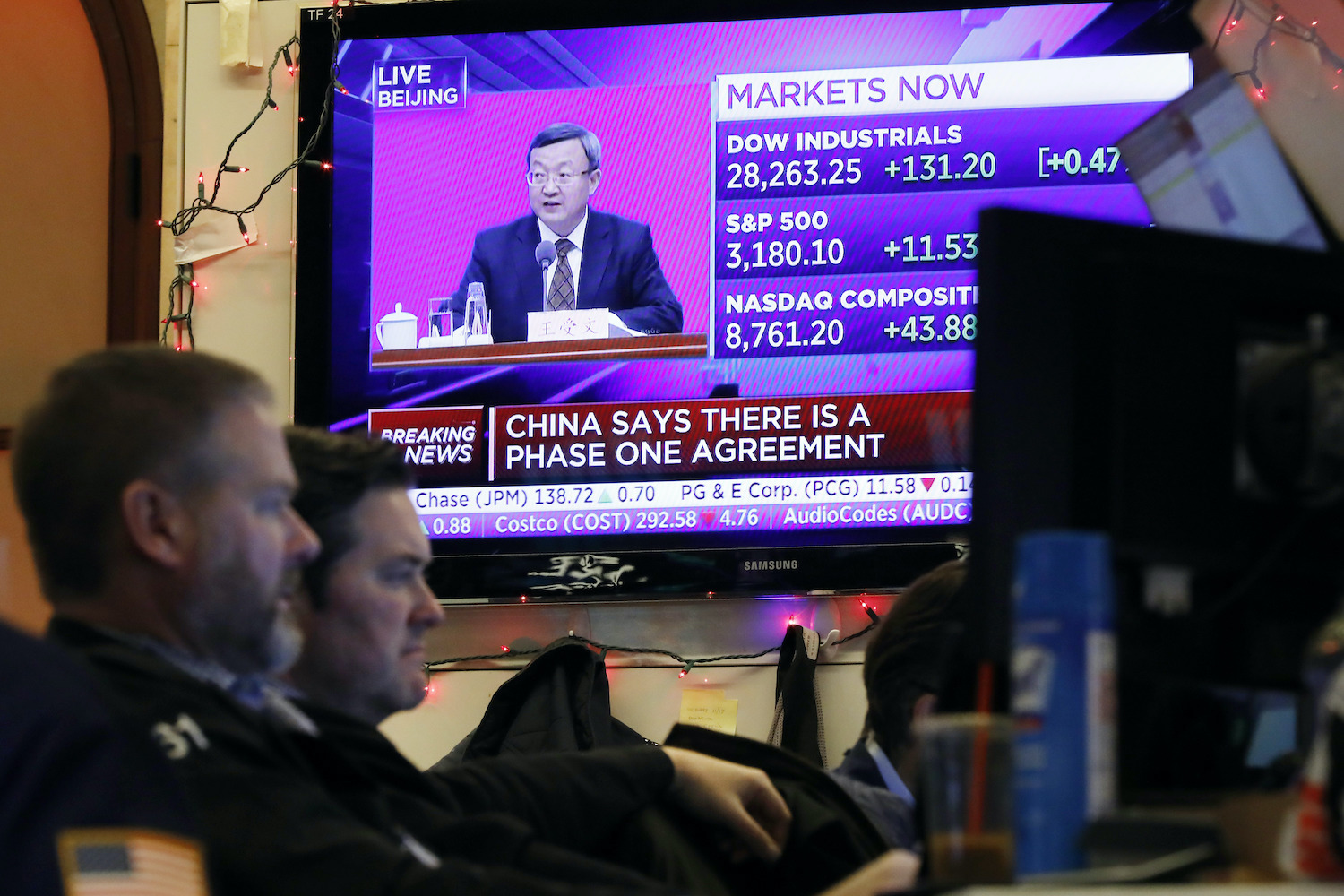 Traders work at the New York Stock Exchange in front of a monitor showing a Chinese official discussing the trade deal with the United States on Friday. (AP Photo)