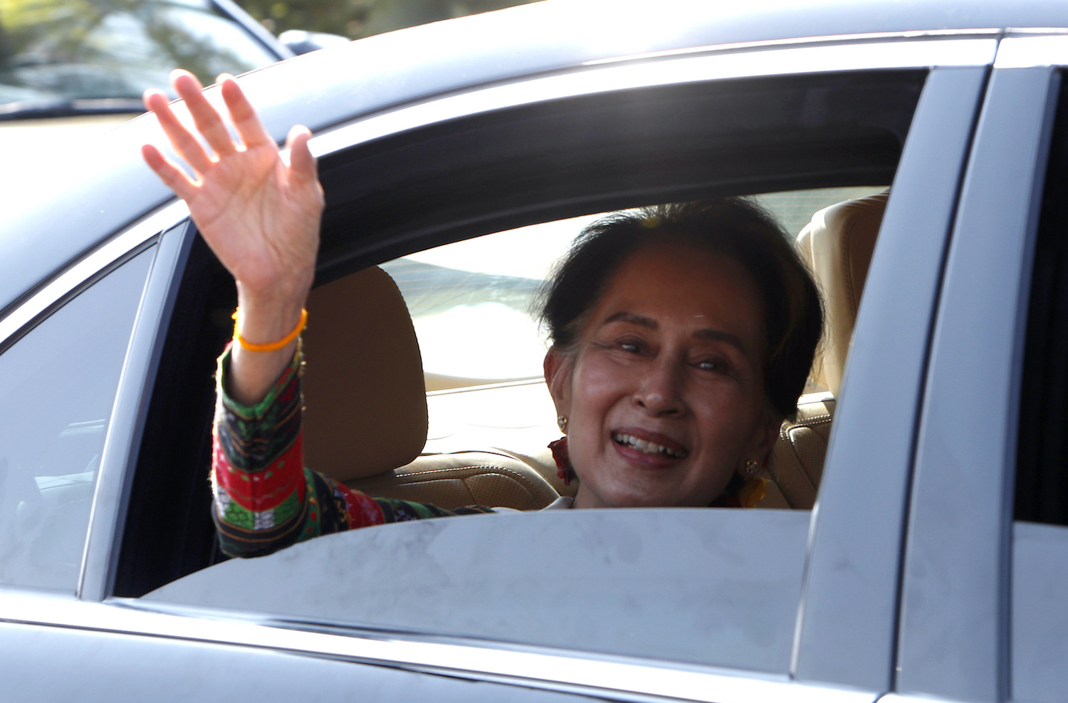 State Counsellor Aung San Suu Kyi waves to supporters from her car outside the airport after arriving in Nay Pyi Taw on Saturday. (AP Photo)