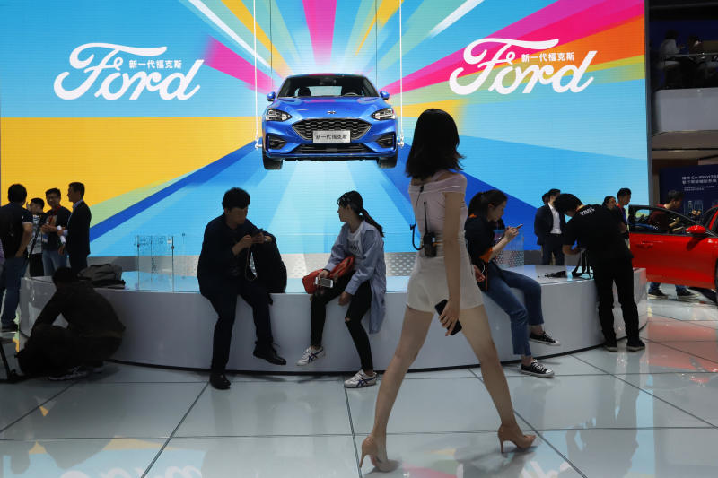 Attendees visit the Ford booth during the Auto China 2018 Show held in Beijing on April 25, 2018. China's government says it will postpone planned punitive tariffs on US-made automobiles and other goods. (AP photo)