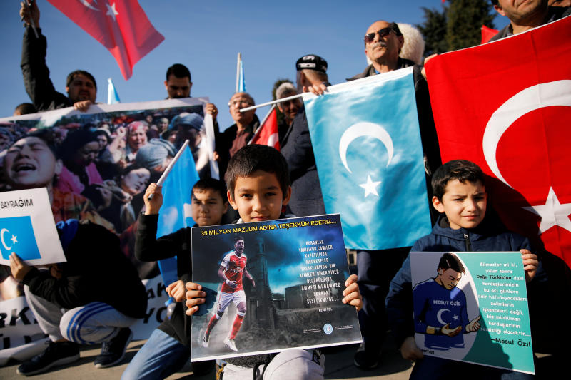 Ethnic Uighur boys hold placards with the images of English soccer club Arsenal's midfielder Mesut Ozil during a protest against China in Istanbul, Turkey on Saturday. The placard reads: