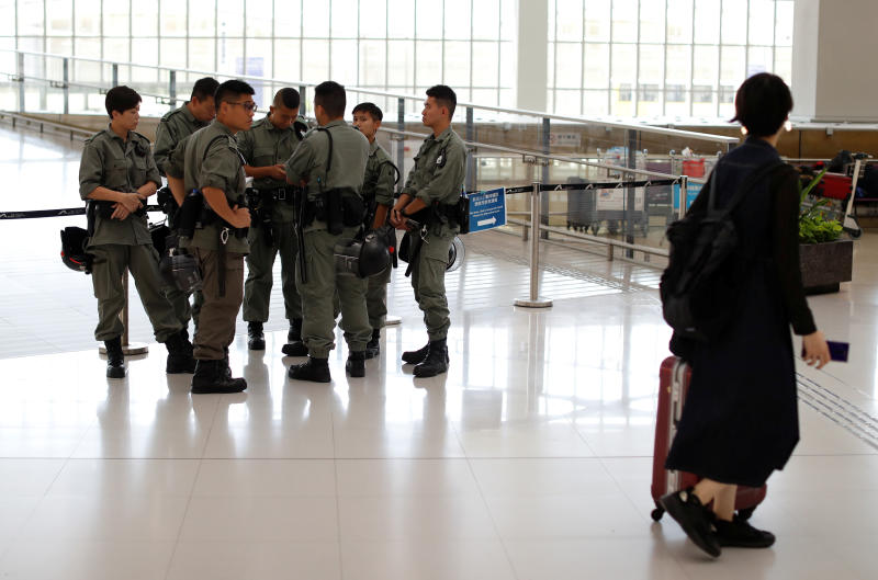 Passenger walks past riot police standing inside Hong Kong International Airport in Hong Kong on Sept 22, 2019. (Reuters photo)