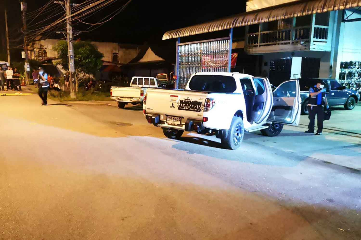 Police cordon off the house and garage where the owner was shot dead by men armed with automatic rifles in Ratsada district of Trang, early Wednesday morning. (Photo by Methee Muangkaew)