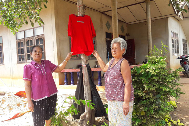 Residents in Nong Bunmak district of Nakhon Ratchasima province on Sunday show a red shirt hung in front of a house to protect them from a ghost. (Photo by Prasit Tangprasert)