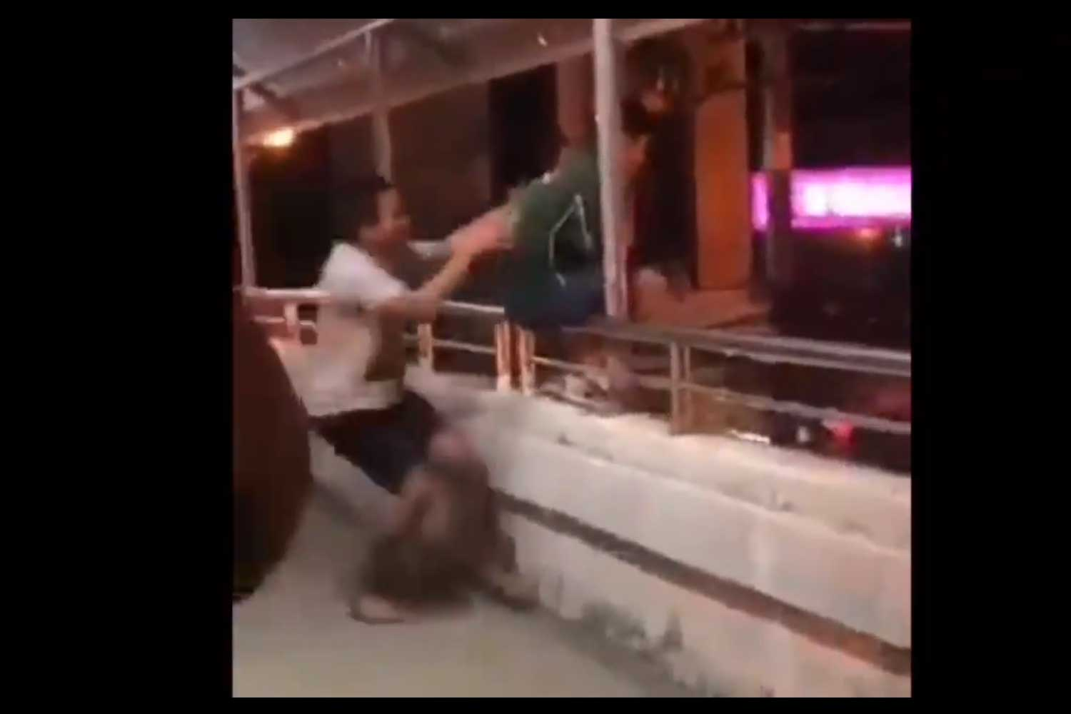 Rescue worker Withawat Sinworasrithaweekhun impersonating an insane man grabs the young man to safety from the handrail of the pedestrian bridge in front of Maejo University in San Sai district, Chiang Mai, Sunday night. (Screenshot from video clip posted on the Guru Chiang Mai Facebook page)
