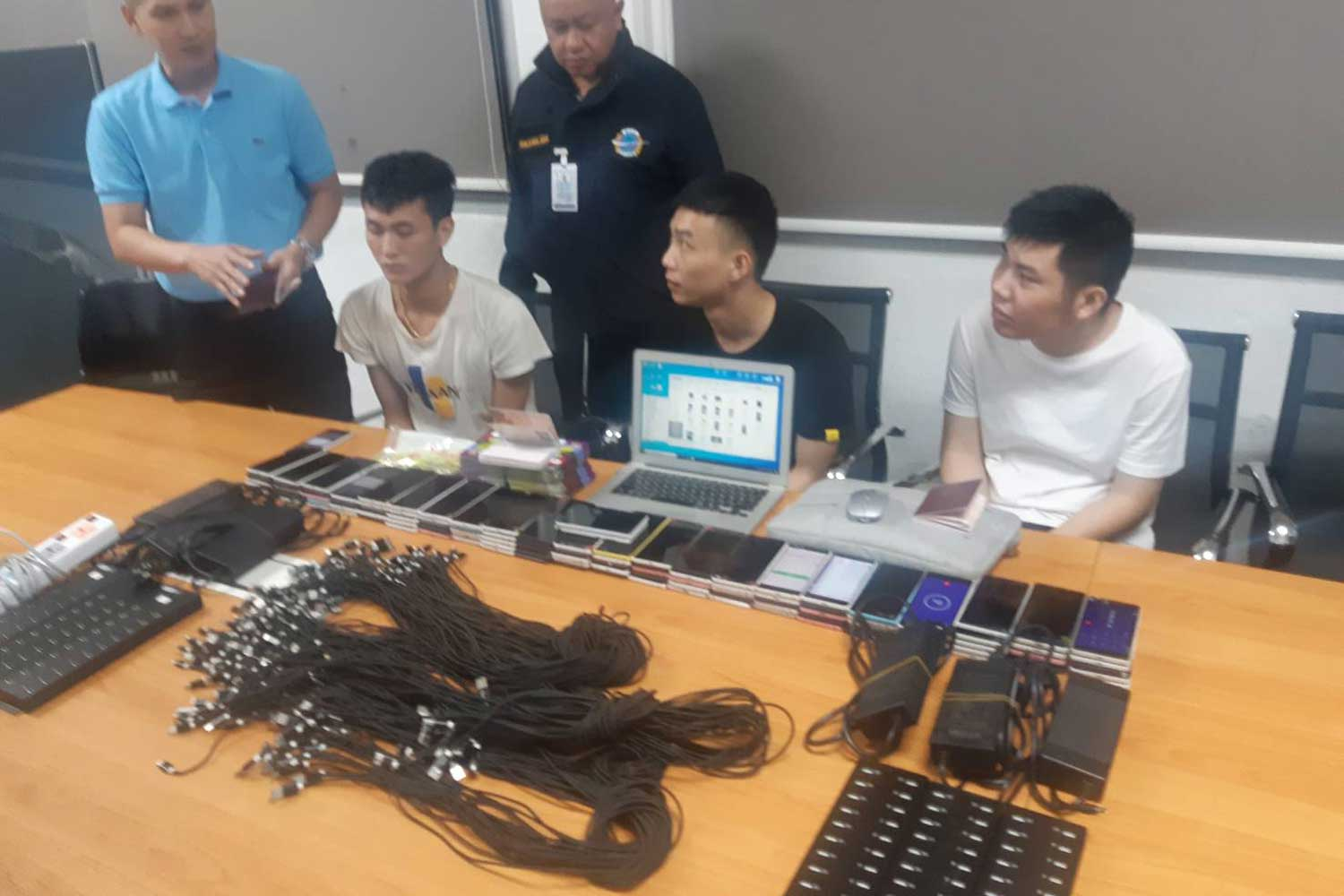 The three Chinese men, aged 23-25, arrested with phones, SIM cards and other related devices for creating fake WeChat accounts for sale on the black market in China. (Police photo)