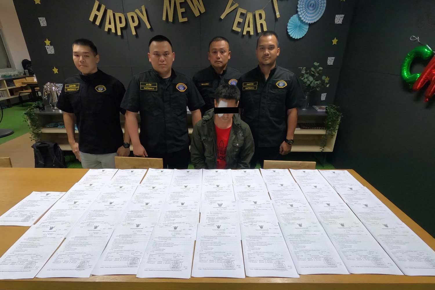 Crime Suppression Division police with Teerapat Puangwijit (seated), arrested for the alleged  embezzlement of 600,000 baht from university students paying tuition fees. (Police photo)