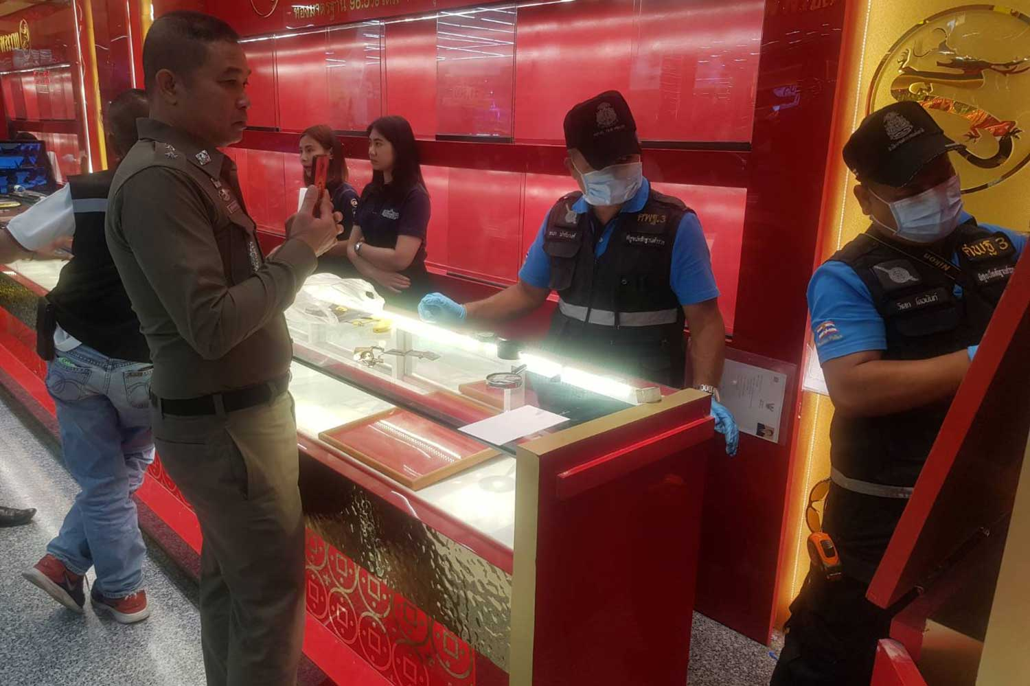 Forensic officers collect fingerprints and other evidence at a gold shop inside a department store in Muang district of Buri Ram on Saturday. (Photo by Surachai Piragsa)