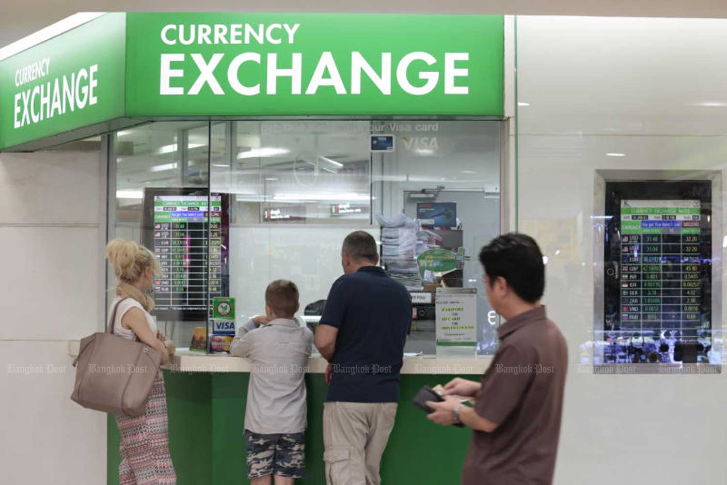 Tourists at a currency exchange booth in Bangkok. The Bank of Thailand on Tuesday advised people not to panic with the unusually strong baht on Monday. (Bangkok Post file photo)