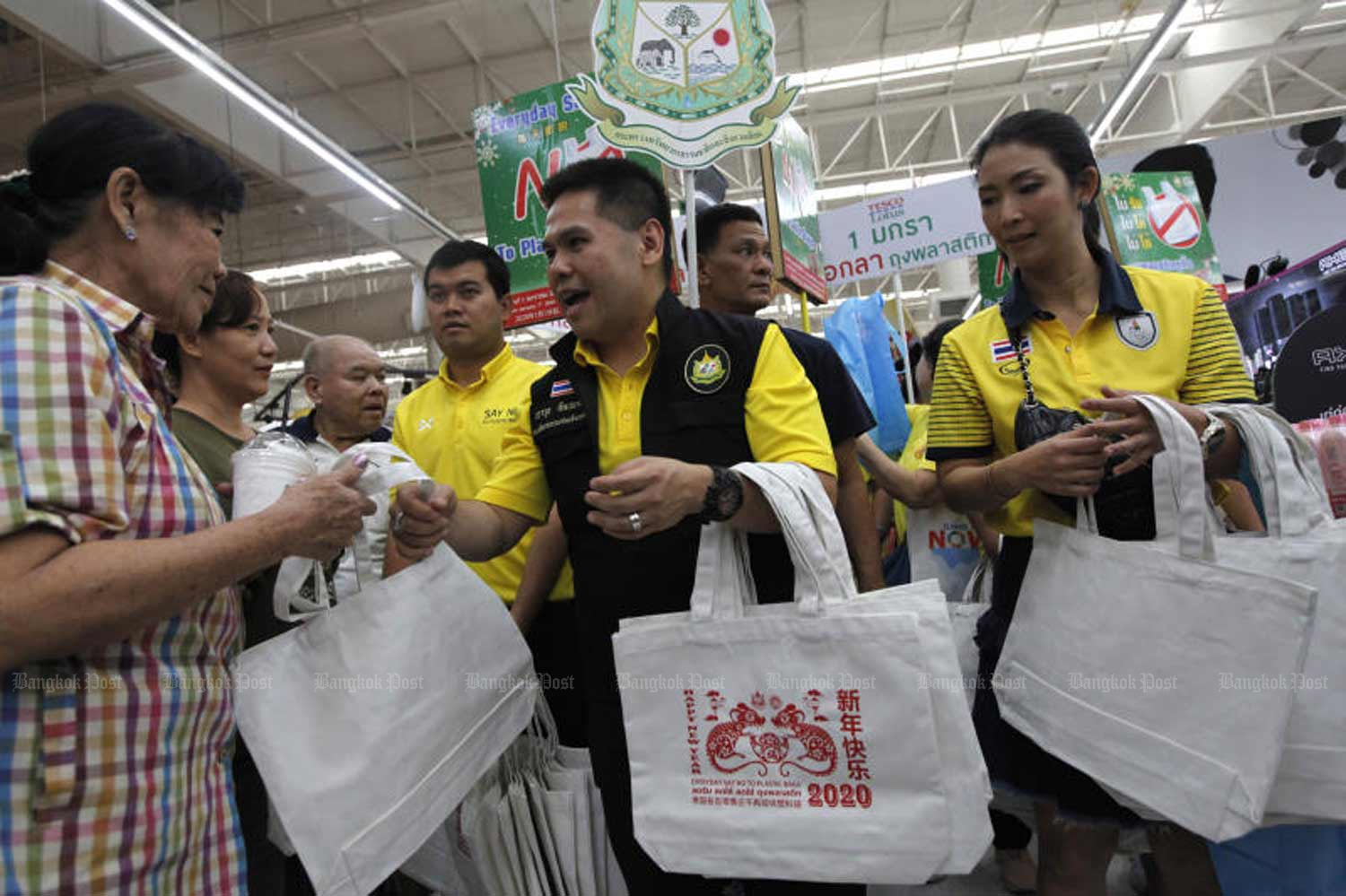 Natural Resources and Environment Minister Varawut Silpa-archa, centre, hands out  reusable cloth bags to shoppers at a superstore in Bangkok on Wednesday, when many stores stopped giving away single-use plastic bags. (Photo by Wichan Charoenkiatpakul)