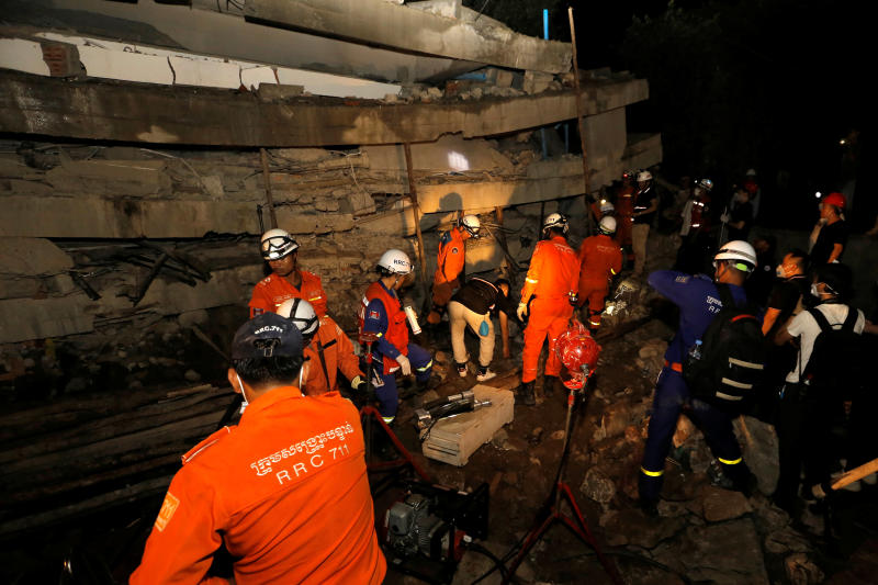 A rescue team searches for trapped workers at a collapsed building which was under construction in Kep, Cambodia, on Friday. (Reuters photo)