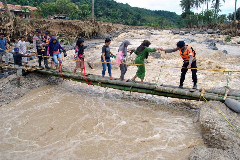 Police officers help people cross an emergency bridge over the Cidurian river in Bogor, Indonesia, on Friday. (Antara Foto/Arif Firmansyah/ via REUTERS)