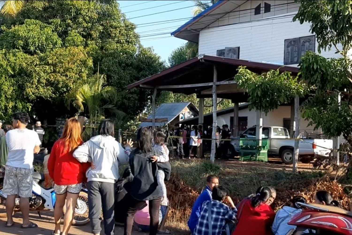 Villagers gather in front of a house where a man killed his wife and two daughters before hanging himself in Phen district of Udon Thani on Sunday morning. (Photo by Yuttapong Kumnodnae)