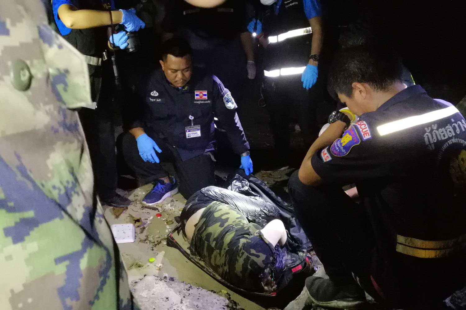 Police and rescue workers inspect the body of a woman found on Bang Phra beach in Si Racha district, Chon Buri, on Friday. (Photo by Jerdsak Saengthongcharoen)