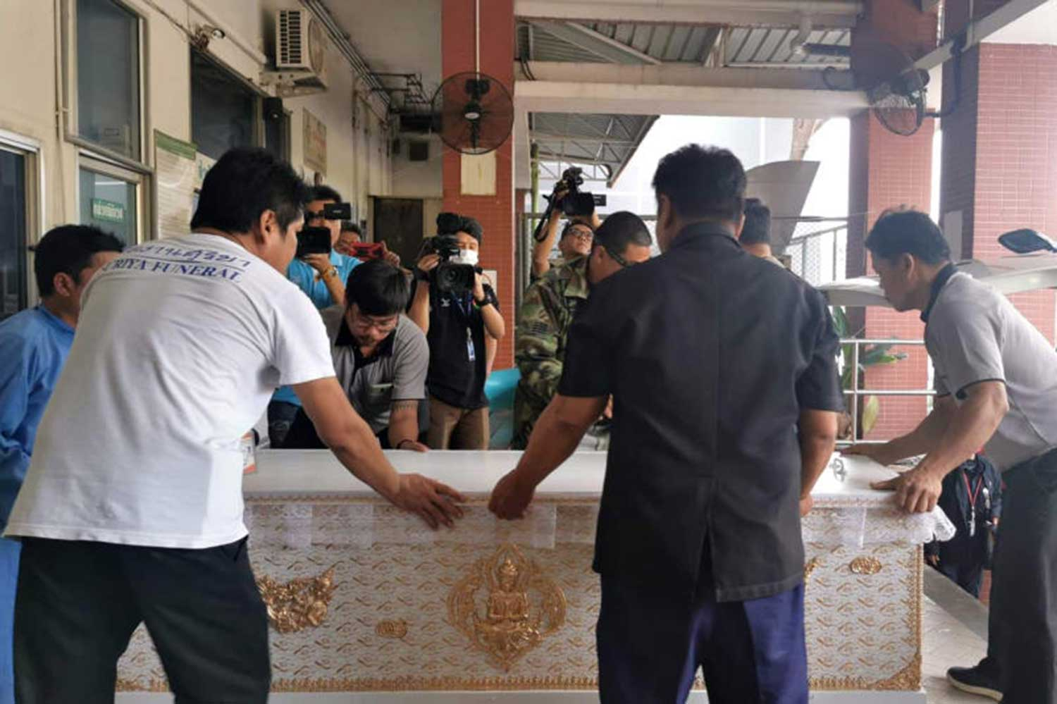 The body of one of three people killed in the gold shop robbery in Lop Buri is taken to a local temple for funeral rites. (Photo by Pongpat Wongyala)