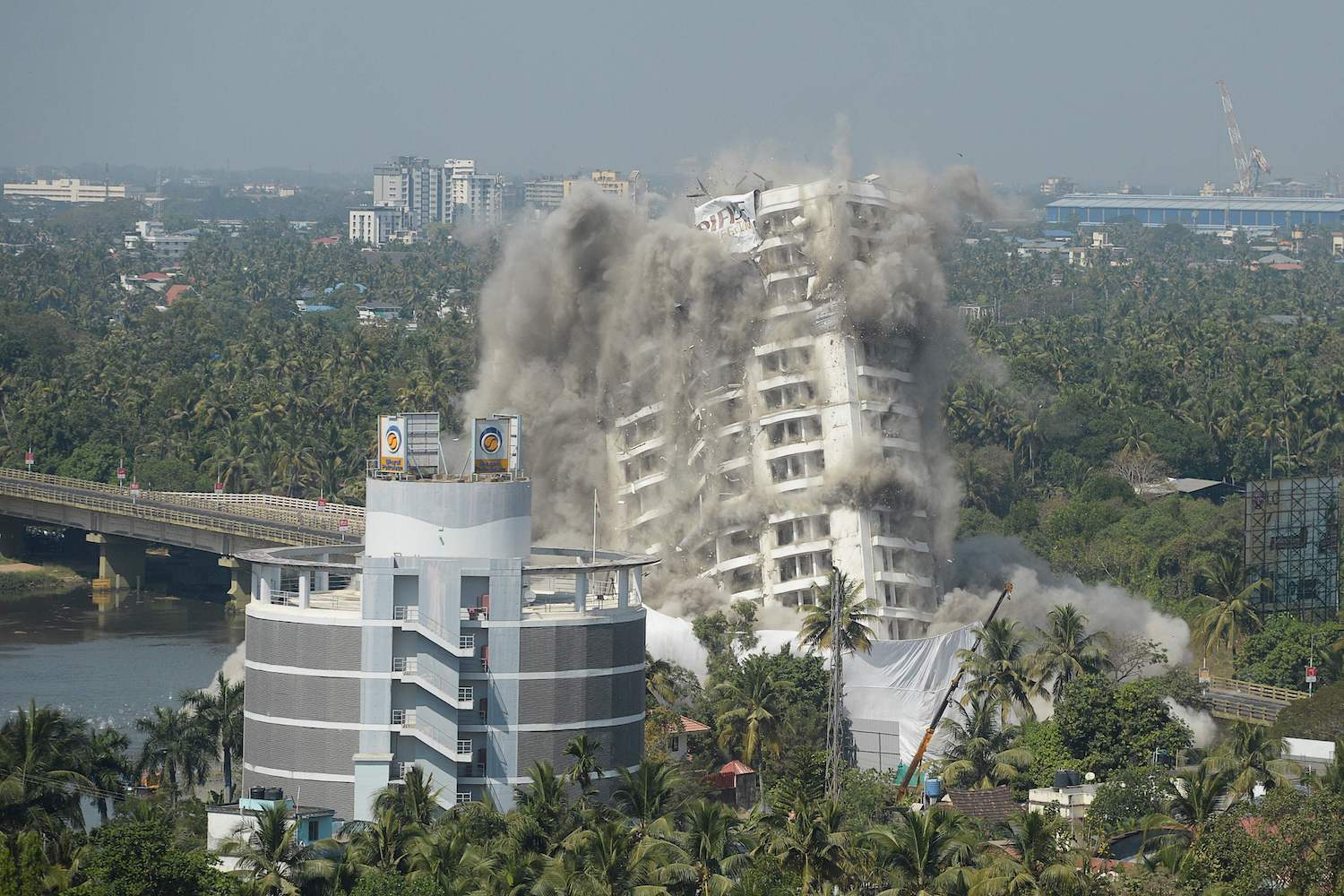 An illegally built apartment complex begins to buckle and collapse during a controlled implosion ordered by the Supreme Court for violating coastal construction regulations in Kochi, India on Saturday. (AFP Photo)