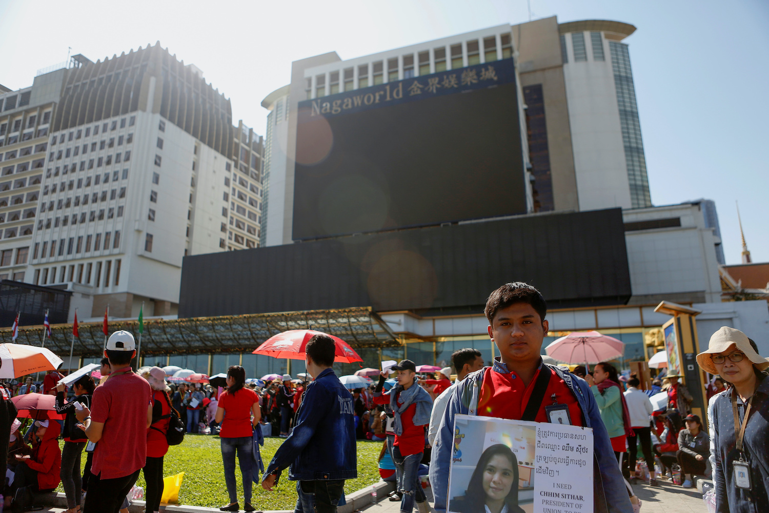 A worker holds up a placard during a protest for higher pay and better working conditions in front of the NagaWorld hotel and casino complex in Phnom Penh on Thursday. (Reuters Photo)