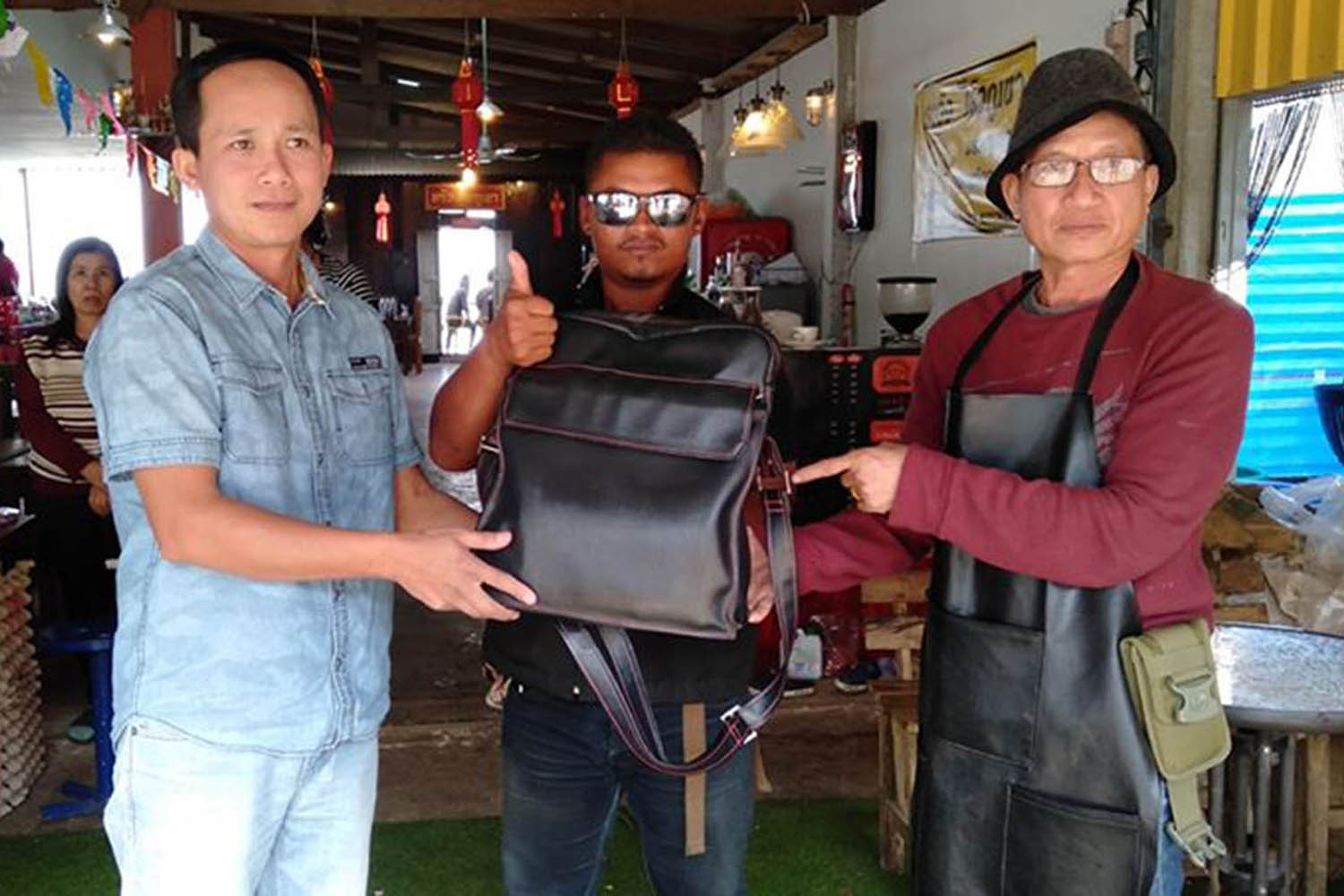 Tourist Pariwat Thangtham (left) retrieves a bag containing 700,000 baht in cash from Mountain Tiger Restaurant owner Chakkrapong Plaichaiyaphum (right), with the administrator of a Facebook page that connected the two as a witness, on Phu Thap Boek in Phetchabun on Sunday. (Photo by Soonthorn Kongwarakhom)