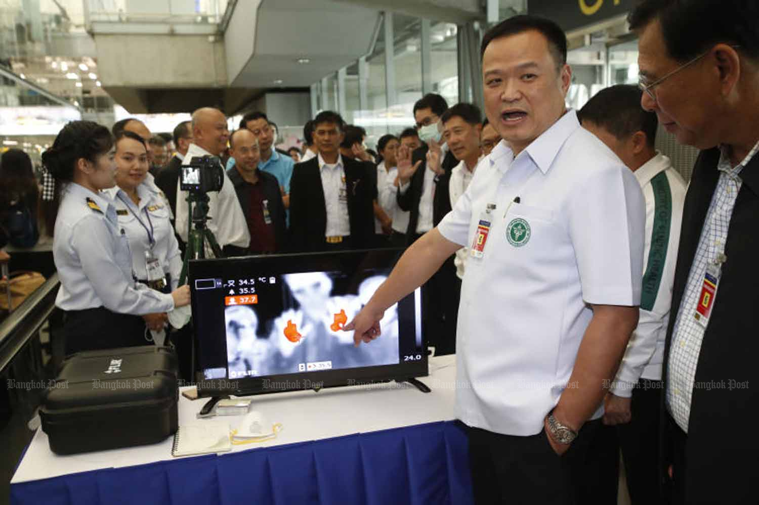 Public Health Minister Anutin Charnvirakul, second right, shows visitors from Wuhan receiving health screening at Suvarnabhumi airport in Samut Prakan province on Jan 5. He said on Monday that a Chinese woman found infected with a new strain of coronavirus was in quarantine and being treated in Nonthaburi province. (Photo by Pornprom Satrabhaya)