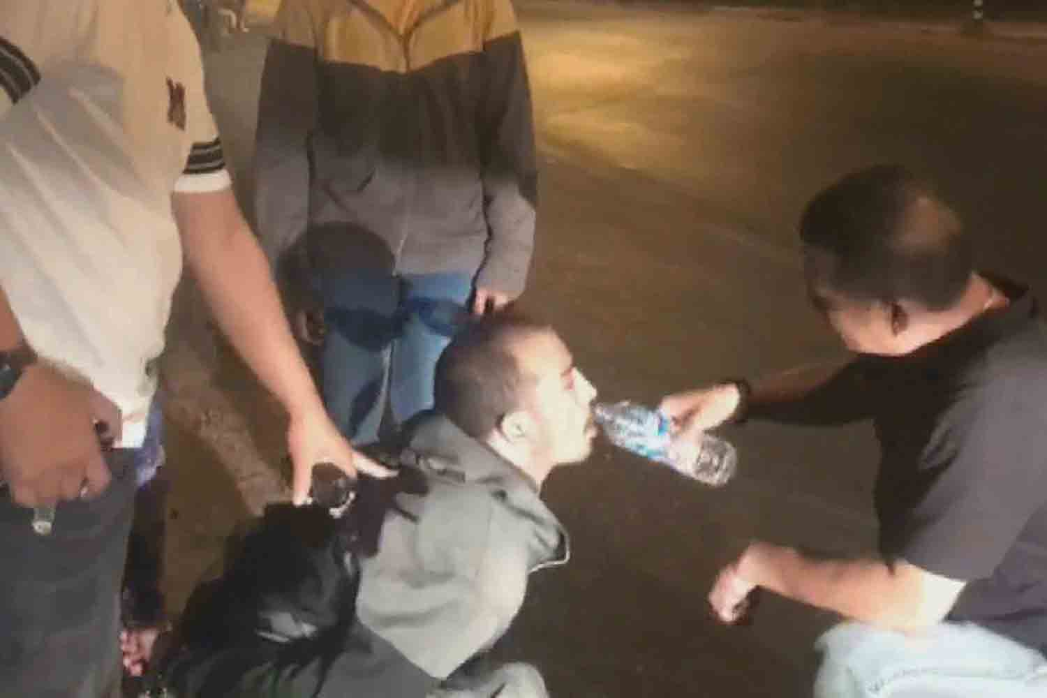 A police officer gives Mulatib, the last of the seven illegal migrants on the run, some water after he was recaptured on the ring road of Mukdahan town late on Monday night. (Photo supplied)