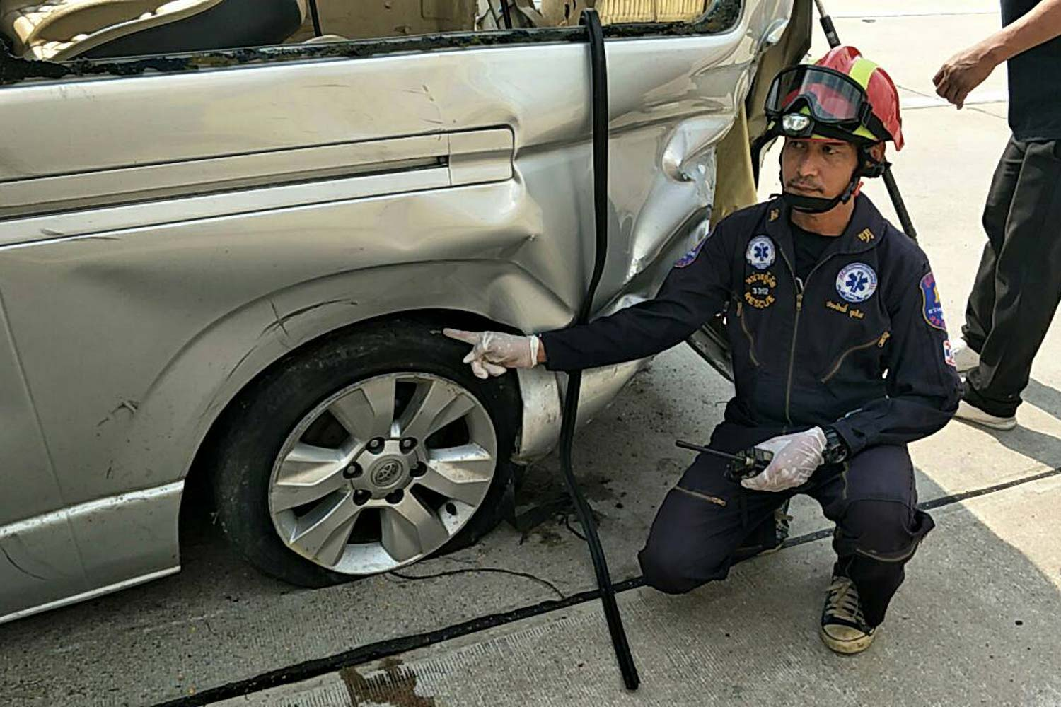 An emergency responder points out the rear tyre the van driver said burst and caused the vehicle to crash into a railing, injuring eight passengers. (Photo: Chaiyot Pupattanapong)